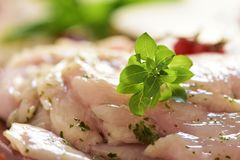 Spiced raw slices of chicken breast Stock Photos