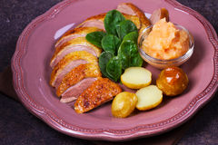Spiced slow roast duck, apple sauce, spinach and potato, served on pink plate Stock Photo
