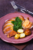 Spiced slow roast duck, apple sauce, spinach and potato, served on pink plate Royalty Free Stock Photos