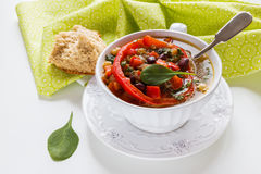 Spiced vegan kidney bean and lentil thick soup with tomatoes and bell pepper. Vintage ceramic bowl on white table Stock Images