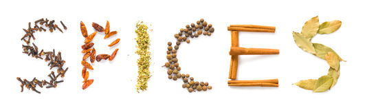 Spices. The word spices written in letters of clove, hot peppers, oregano, allspice, cinnamon sticks and bay leaves. Isolated on white royalty free stock photo