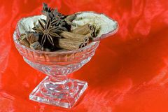 Spices. Christmas spices cinnamon, anise and dried apple slices in a glass bowl with red background Stock Photography