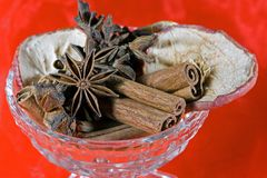 Spices. Christmas spices cinnamon, anise and dried apple slices in a glass bowl with red background Royalty Free Stock Images