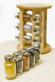 Spices. A set of small glass containers with spices, shallow depth of field, focus on the first one with curry inside. A wooden rack blurred in the background Stock Photos