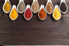 Spices. Aromatic and colorful spices in ceramic containers on a wooden background. Spice in the kitchen stock photography