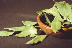 Spices of bay leaf in rural style/bay leaf in a wooden bowl on a black stone background. selective focus stock images