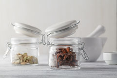 Spices on black background in special jars. Stock Photos
