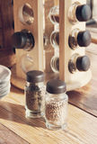 Spices in bottles. Spices in the bottles containing coriander seeds and oregano on the wooden kitchen table Stock Image