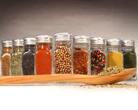 Spices in bottles with wooden spoon Stock Image
