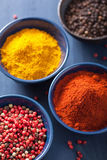 Spices in bowls: curry pink and black pepper paprika powder Stock Image