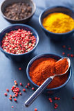 Spices in bowls: curry, pink black pepper, paprika powder Royalty Free Stock Photo