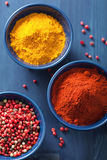 Spices in bowls: curry pink and black pepper paprika powder Royalty Free Stock Photo
