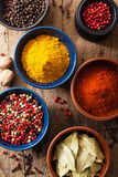 Spices in bowls: pink black pepper, paprika powder, curry, bay l Stock Photo