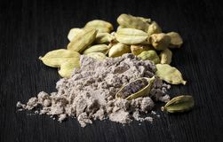 Spice; cardamom pods and powder on a dark background royalty free stock image