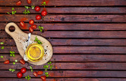 Spices, cherry tomatoes, basil and vegetable oil on dark wooden table, top view stock images