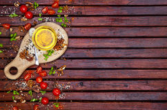 Spices, cherry tomatoes, basil and vegetable oil on dark wooden table, top view stock photos