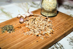 Spices and chopped walnuts on wooden board. Finely ground walnut, spices and young garlic Royalty Free Stock Photo