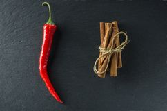 Spices cinnamon and red hot pepper on the background of slate. Top view Royalty Free Stock Photos