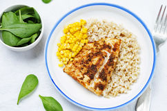 Spices Cod with brown rice, spinach and corn Royalty Free Stock Photography