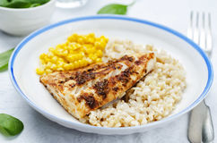 Spices Cod with brown rice, spinach and corn Royalty Free Stock Image