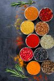 Spices. Colorful spices. Curry, Saffron, turmeric, cinnamon and otheron a dark concrete background. Pepper. Large collection of di Stock Photography