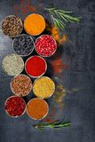 Spices. Colorful spices. Curry, Saffron, turmeric, cinnamon and otheron a dark concrete background. Pepper. Large collection of di Stock Photo