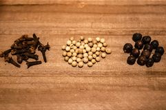 Small piles of cloves, white pepper seeds and juniper on the wooden background stock photography