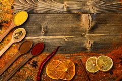 Spices concept. Spices scattered all over wooden surface. Spoons with spices on wooden texture. Spoons filled with. Cinnamon, grinded red pepper and curcuma royalty free stock images