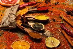 Spices concept. Spices scattered all over wooden surface. Spoons filled with cinnamon, grinded red pepper and curcuma. Powder and kitchen herbs scattered on stock photography