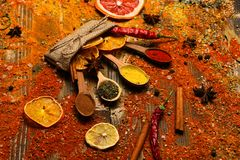 Spices concept. Spices scattered all over wooden surface. Spoons with spices on wooden texture. Spoons filled with. Cinnamon, grinded red pepper and curcuma royalty free stock photography