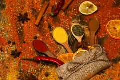 Spices concept. Spoons with spices on wooden texture. Spices scattered all over wooden surface. Spoons filled with. Cinnamon, grinded red pepper and curcuma royalty free stock photo