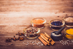 Spices and condiment for cooking. Turmeric, pepper, barberry, cinnamon, carnation on the table. Warm toned. Copy space at the top Stock Images