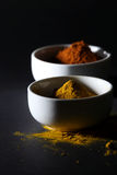 Spices in cups on a black background. Two white cups containing a spice powder on a black background Royalty Free Stock Photo