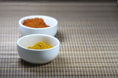 Spices in cups on a mat background. Two white cups containing a spice powder on a mat background. Space left on the right side for custom text Royalty Free Stock Images