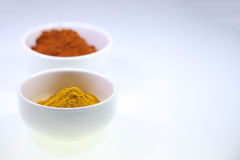 Spices in cups on a white background. Two white cups containing a spice powder on a white background. Space left on the right side for custom text Stock Photo