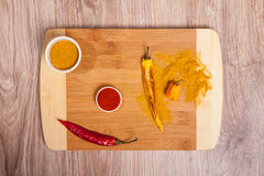 Spices on cutting board whit hot chili and Habanero. Culinary composition on wood table background in kitchen. Glass bowl with cur Stock Image