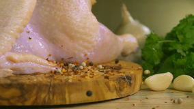 Spices are falling on a wooden board with raw chicken stock video footage