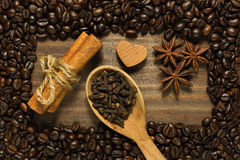 Spices framed by roasted coffee beans. Cinnamon sticks, anise and clove in wooden spoon on the wooden table with frame of roasted coffee beans royalty free stock photos