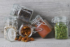 Spices in glass jars. Some glass jars with different spices on a wooden stand stock image