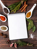 Spices, herbs and empty notebook on the table Royalty Free Stock Images