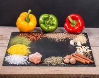 Spices, herbs and fresh pepper on slate tray on an old rustic table. Red, yellow and green fresh peppers. Top view. royalty free stock images