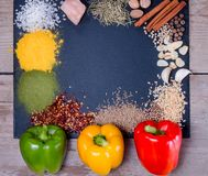 Spices, herbs and fresh pepper on slate tray on an old rustic table. Red, yellow and green fresh peppers. Top view. stock image