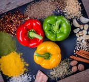 Spices, herbs and fresh peppers on slate tray on an old rustic table. Red, yellow and green fresh peppers. Top view. Rustic style. stock photography