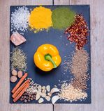 Spices, herbs and fresh yellow pepper on slate tray on an old rustic table. Top view. Rustic style. Fresh ingredients. stock photos