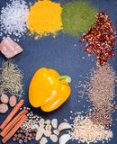 Spices, herbs and fresh yellow pepper on slate tray on an old rustic table. Top view. Rustic style. stock photography