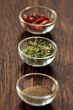 Spices and herbs in glass bowls. Stock Photo