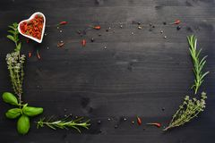 Spices and herbs isolated on a dark wooden table royalty free stock photography