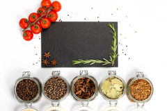 Spices and herbs in jars. Food, cuisine ingredients. Cherry branch. Stock Photos