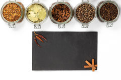 Spices and herbs in jars. Food, cuisine ingredients. Wooden board Stock Images