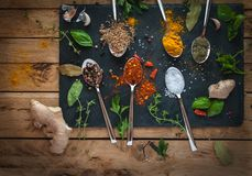 Spices and herbs in spoons dark background, top view royalty free stock photography